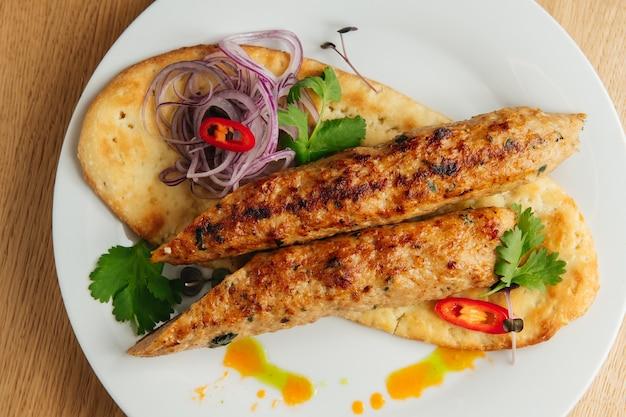 Poulet lula kebab avec pain pita. vue de dessus