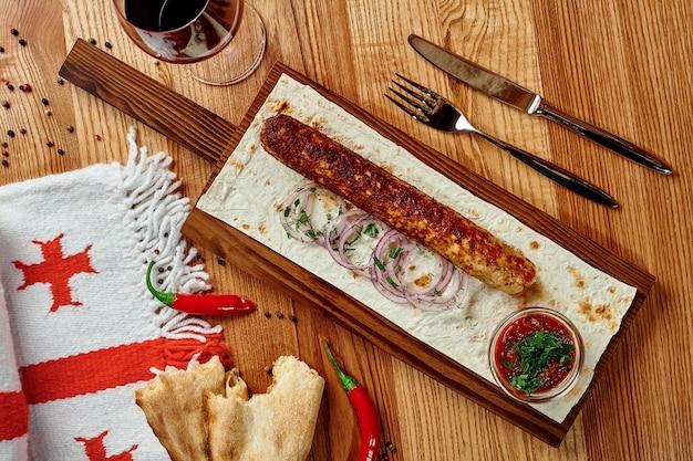 Poulet lula kebab sur table en bois avec oignons verts lavash et satsebeli