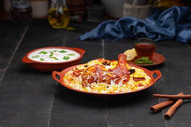 Poulet mandi biryani avec raita en accompagnement disposé dans une faïence