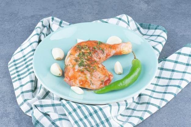 Poulet mariné à l'ail et au poivre sur assiette bleue.