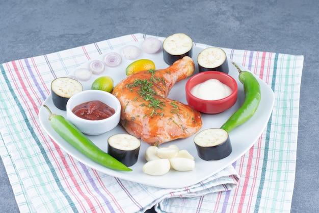 Poulet mariné sur assiette avec des légumes tranchés.