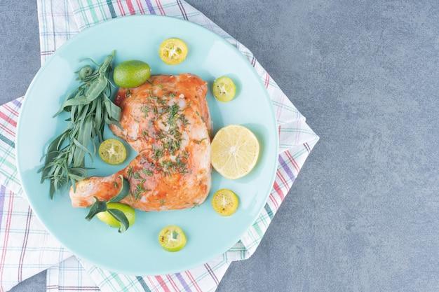 Poulet mariné à l'estragon citronné sur plaque bleue.