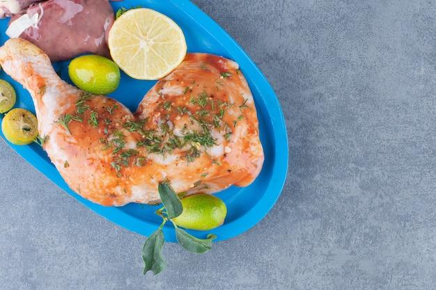 Poulet mariné et viande sur assiette bleue.