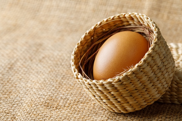 Poulet ou œuf de poule dans un panier en osier sur un sac