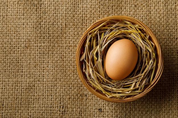 Poulet ou œuf de poule sur paille dans un panier en osier sur un sac