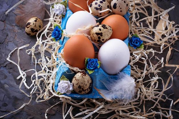 Poulet et oeufs de caille dans une boîte en carton, concept de pâques. mise au point sélective