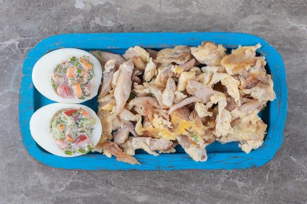 Poulet et œufs durs avec salade sur plaque bleue.