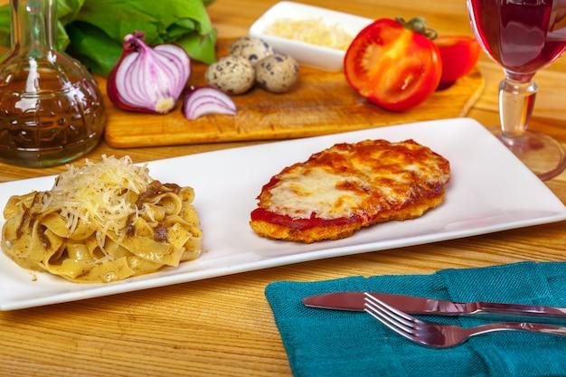 Poulet parmigiana et spaghettis se bouchent sur une assiette sur la table.