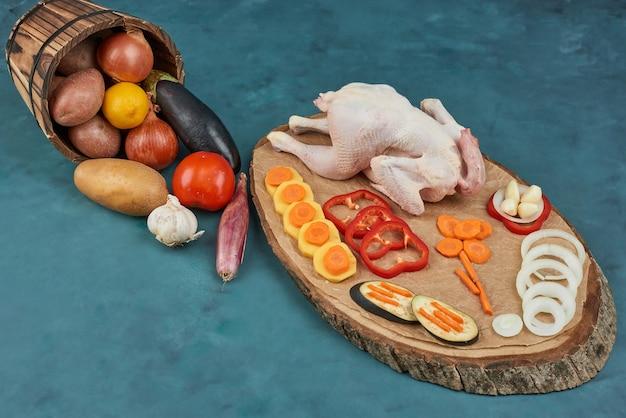 Poulet sur une planche de bois avec des légumes dans le seau.