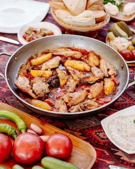 Poulet et pommes de terre grillées dans une casserole avec une sauce grasse, légumes autour.