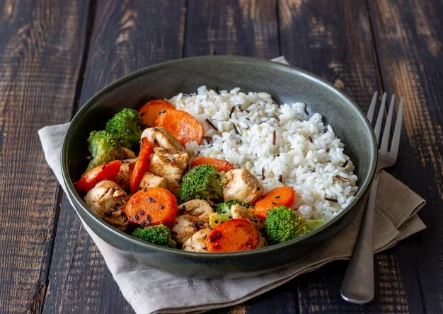 Poulet avec riz, brocoli, carottes et sauce soja. alimentation équilibrée. régime. recette.