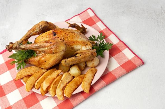Poulet rôti appétissant avec pommes de terre à l'ail et oignons