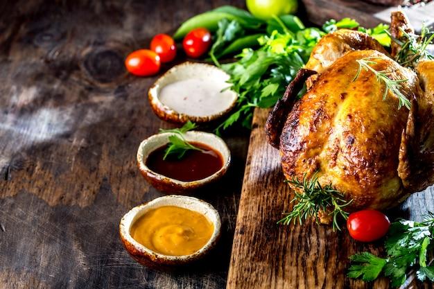 Poulet rôti au romarin servi sur une plaque noire avec des sauces sur une table en bois, vue de dessus.
