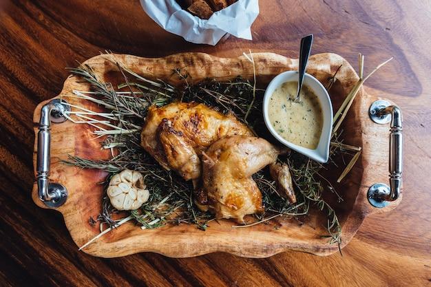 Poulet rôti aux herbes, romarin et ail dans un plateau en bois servi avec une sauce blanche.
