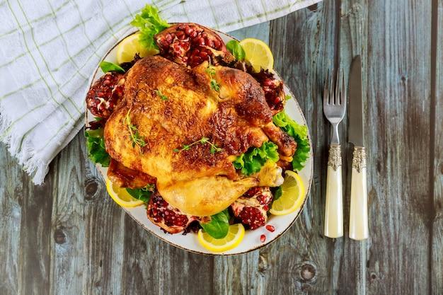 Poulet rôti entier sur plaque blanche avec salade, grenade et fourchette.