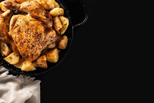 Poulet rôti maison avec pommes de terre sur fond d'ardoise noire