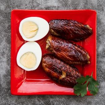 Poulet rôti avec œuf à la coque dans une assiette rouge sur un sol en béton
