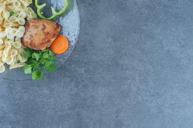 Poulet rôti et pâtes savoureuses sur plaque de verre.