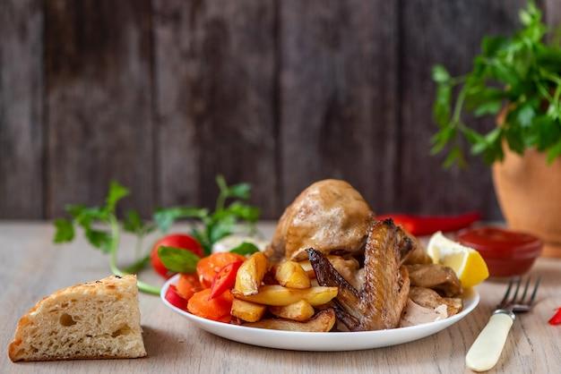 Poulet rôti, pommes de terre et légumes en assiette sur bois. vue de côté.