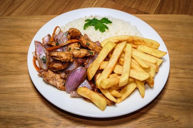 Poulet saltado alimentaire péruvien, frites, poulet assaisonné, oignons, tomates, légumes rôtis, arros blancs sur une assiette blanche.
