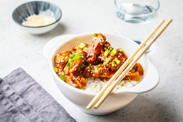 Poulet teriyaki asiatique avec riz, sésame et oignons verts dans un bol blanc.