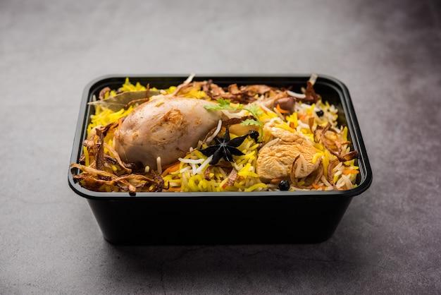 Poulet tikka biryani de style restaurant emballé pour la livraison à domicile dans une boîte ou un conteneur en plastique avec raita et salan