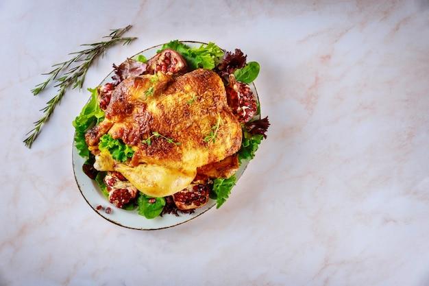 Poulet traditionnel entier rôti sur une assiette avec grenade, romarin et salade verte.