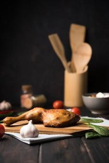 Poulet vue de face sur planche de bois avec des ingrédients