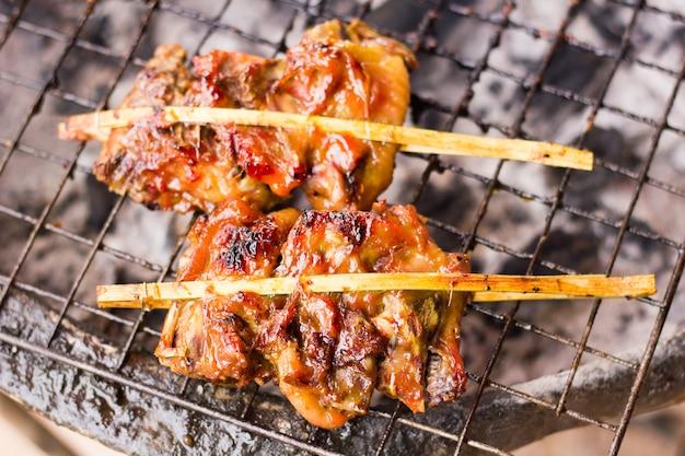 Poulets grillés sur un poêle en fer, une cheminée, un bâton de poulet grillé traditionnel de style thaïlandais.