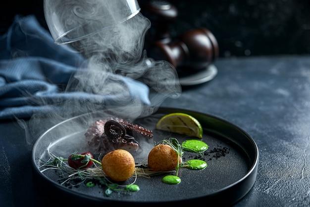 Poulpe grillé grillé servi avec de la fumée sous le capot, spectacle alimentaire, discret.