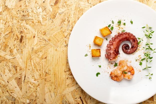 Poulpe grillé sur plaque de restaurant blanc servi avec des crevettes