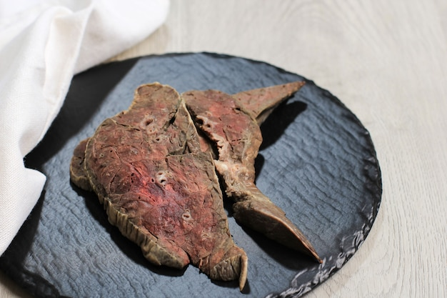 Poumon de vache bouilli sur planche à découper en bois, prêt à l'assaisonnement ou à la cuisson
