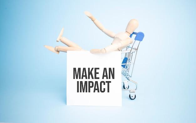 Poupée en bois dans un magasin avec du papier blanc et signe make an impact. concept d'entreprise