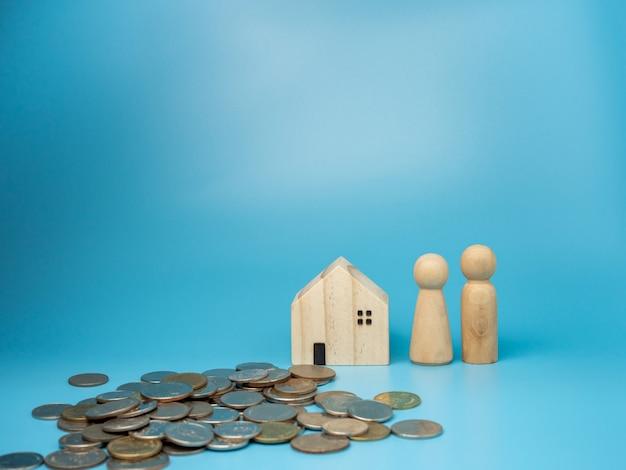 Une poupée en bois debout à côté d'une réplique de maison en bois et un tas d'argent sur bleu