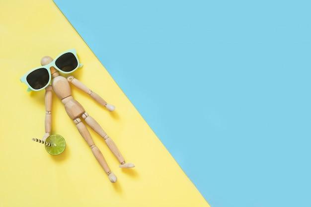 Poupée en bois avec des lunettes de soleil sur jaune. uv de protection.