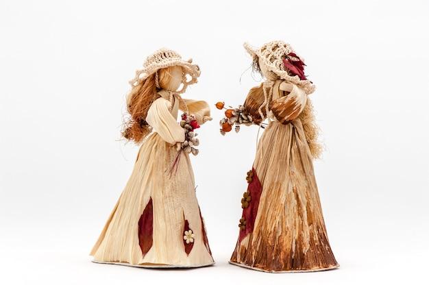 Poupée de feuilles de maïs mains avec fleurs o blanc