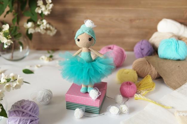 Une poupée en fil de laine. jouet en peluche tricoté à la main sur une table en bois.