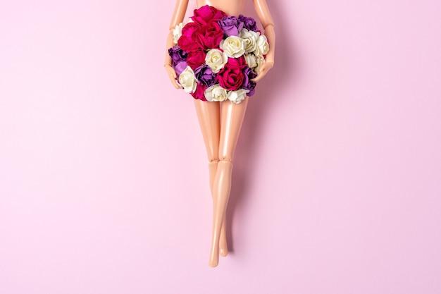 Poupée fille avec des fleurs colorées sur fond rose.
