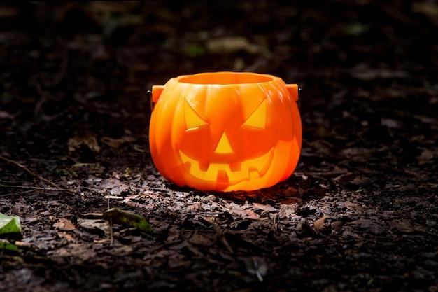 Poupée halloween citrouille posée sur le sol.