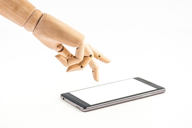 Poupée de main en bois touchant un téléphone intelligent sur fond blanc