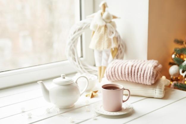 Poupée à la main avec service à thé et guimauves près de la fenêtre. petit-déjeuner d'hiver confortable. concept et humeur de noël.