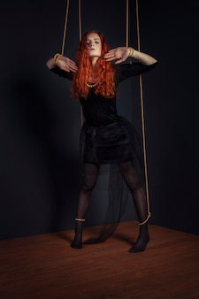 Poupée marionnette halloween rousse femme attachée avec des cordes. poupée fille attachée avec des cordes avec les mains et les pieds