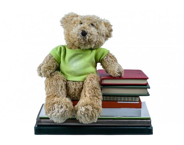 Poupée mignonne ours brun assis sur de nombreux livres isolés sur blanc