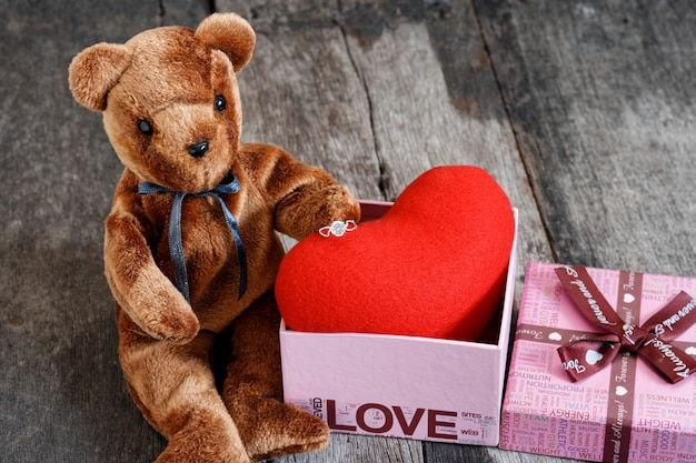 Poupée ourson et la bague avec un coeur rouge.