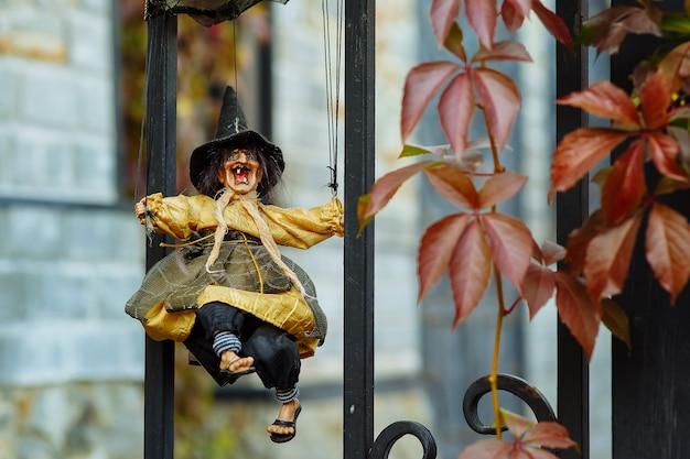 Une poupée sorcière effrayante sur un treillis en fer forgé parmi les plantes d'automne