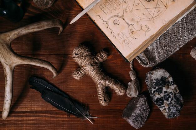 Une poupée vaudou en corde se trouve avec un vieux livre grimoire