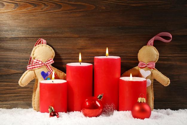 Poupées en feutre, bougies rouges et boules dans la neige