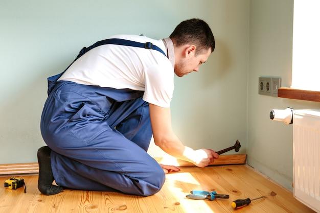 Pour faire des réparations. installation d'une nouvelle plinthe. un homme fait des réparations dans une pièce