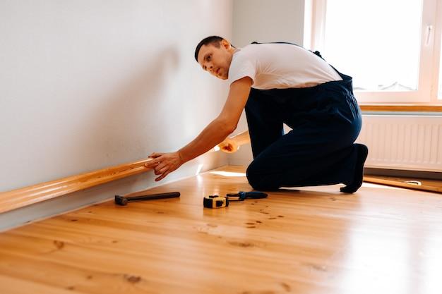 Pour faire des réparations. pose d'une nouvelle plinthe. un homme fait des réparations dans une pièce