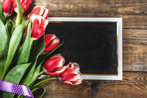 Pour félicitations, cartes de voeux. fleurs de tulipes de printemps frais avec tableau noir pour le texte, sur une vue de dessus en bois